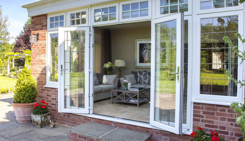 An open white uPVC french door and classic tiled flooring