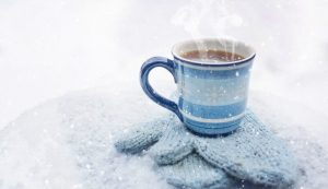 A hot drink atop a pair of gloves.