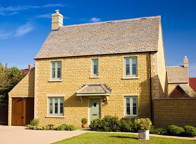 Yellow stone house with chartwell green uPVC casement windows