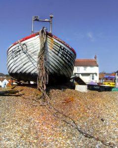 Old boat outside seaside home.
